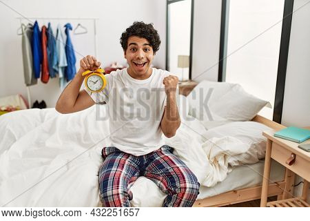 Young hispanic man holding alarm clock sitting on the bedroom screaming proud, celebrating victory and success very excited with raised arms