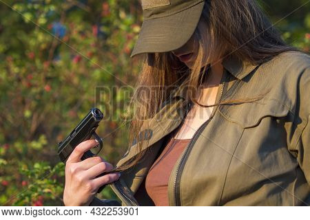A Girl In An Unbuttoned Green Military Jumpsuit Stands Against The Background Of Red Bushes And Rose
