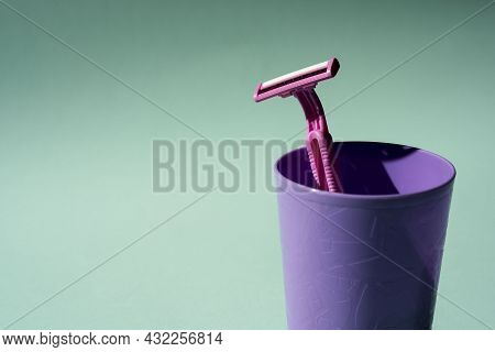 Disposable Razor In A Purple Glass, A Creative Composition Of A Disposable Razor On A Turquoise Back