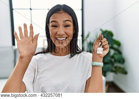 Young hispanic woman holding keys of new home waiving saying hello happy and smiling, friendly welcome gesture