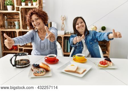 Family of mother and down syndrome daughter sitting at home eating breakfast approving doing positive gesture with hand, thumbs up smiling and happy for success. winner gesture.