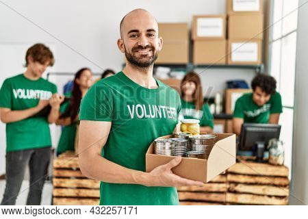 Group of young volunteers working at charity center. Man smiling happy and holding box with food to donate.