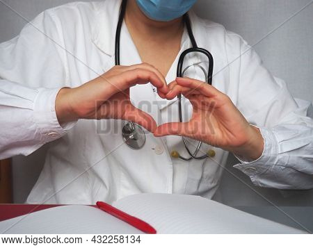 Doctor In A Mask And With A Stethoscope Shows The Heart With His Hands. Notebook And Pen On The Tabl