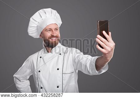 Optimistic Bearded Man In Chef Uniform Smiling And Taking Selfie Via Smartphone During Work Against