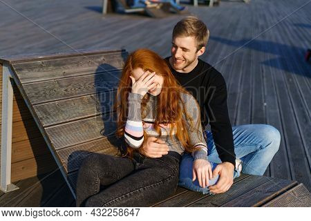 A Young Couple In Love, A Man And A Woman, Embrace On A Bench In The Recreation Area. A Beautiful Re
