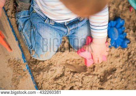Child Plays In Sandbox With Toys. Toddler Hands With Sand And Copy Space.