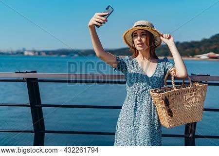 Attractive Redhead Woman Posing At Sunny Day. Making Selfie Using Phone. Walks Along The Pier Near T