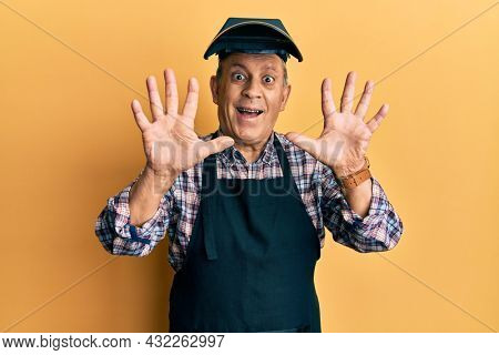 Handsome senior man with grey hair wearing welding protection mask showing and pointing up with fingers number ten while smiling confident and happy.