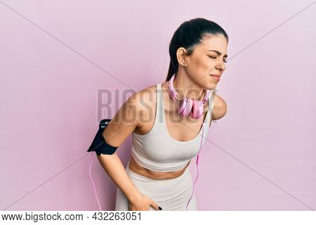 Young hispanic woman wearing gym clothes and using headphones suffering of backache, touching back with hand, muscular pain