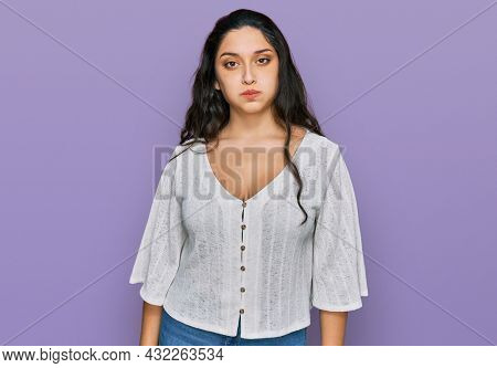 Brunette young woman wearing casual clothes puffing cheeks with funny face. mouth inflated with air, crazy expression.