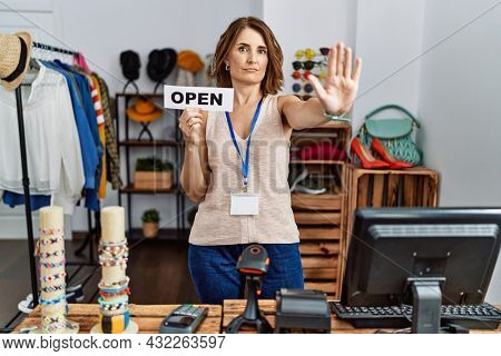 Middle age woman holding banner with open text at retail shop with open hand doing stop sign with serious and confident expression, defense gesture