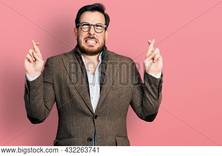Young hispanic man wearing business jacket and glasses gesturing finger crossed smiling with hope and eyes closed. luck and superstitious concept.