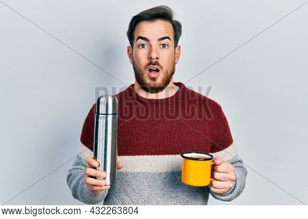Handsome caucasian man with beard drinking a cup of coffee holding thermo afraid and shocked with surprise and amazed expression, fear and excited face.