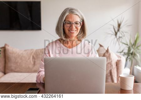 Happy middle age senior woman sitting at the table at home working using computer laptop  with smile on face, natural expression.Smiling mature gray-haired female talking online chat with friends