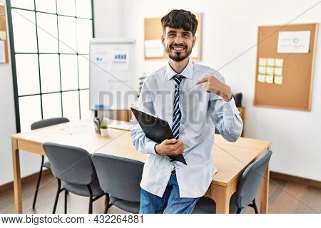 Hispanic man with beard wearing business style sitting on desk at office pointing finger to one self smiling happy and proud