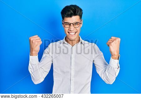 Young hispanic man wearing casual clothes and glasses screaming proud, celebrating victory and success very excited with raised arms
