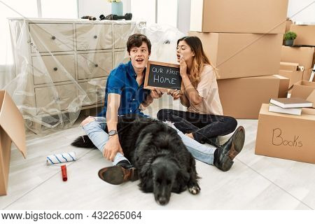 Young caucasian couple with dog holding our first home blackboard at new house hand on mouth telling secret rumor, whispering malicious talk conversation