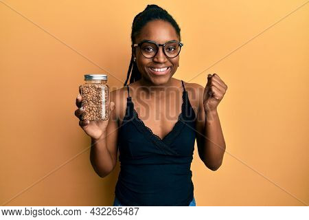 African american woman with braided hair holding lentils screaming proud, celebrating victory and success very excited with raised arm