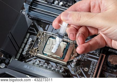 A Technician Applies White Thermal Paste To The Cpu Intel I7-9700k. Installing A Cooler On A Pc Proc