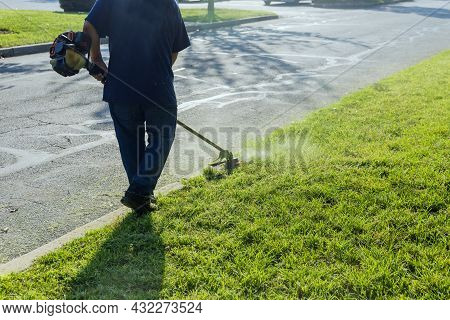 A Lawn Mower Mows Fresh, Green Grass On The Lawn Near A Municipal Worker With Lawn Mower In His Hand