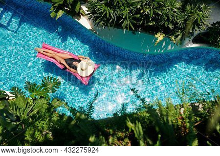 Beautiful Young Woman In Black Swimsuit And Straw Hat Floating On Pink Mattress In Swimming Pool
