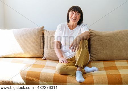 Happy Mature Woman Relaxing On Sofa At Home In Living Room. Portrait Of Beautiful Caucasian Woman Sm