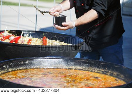 The cook cooks food outside in large vats on coals in the open air. High quality photo