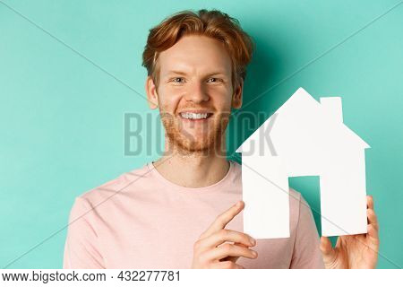 Real Estate Concept. Close Up Of Redhead Bearded Man In T-shirt Showing Paper House Cutout, Smiling