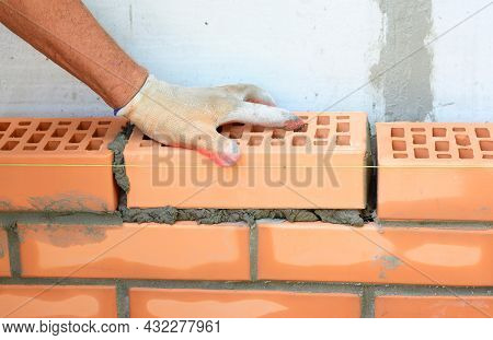 Masonry And Brickwork. A Mason Is Laying Face Clay Bricks Next To Concrete Block Wall. Cavity Wall C