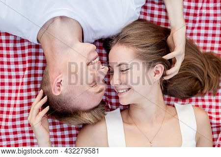 Young Couple Cuddling On A Picnic Blanket, Top View