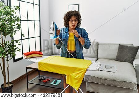 Young hispanic woman ironing clothes at home feeling unwell and coughing as symptom for cold or bronchitis. health care concept.