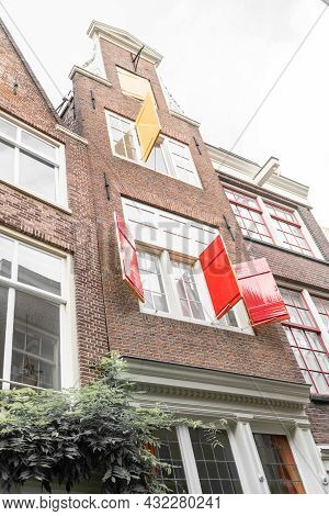 Low Angle View From Street Of Typically Dutch Row House With Gable, Windows And Colored Shutters Ope