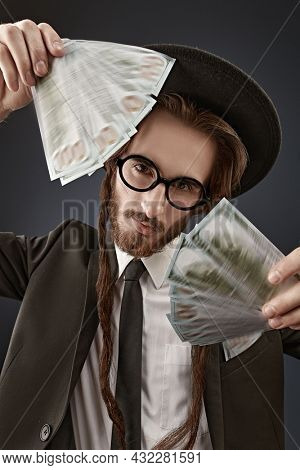 Portrait of a wealthy Jewish man with  a bundle of banknotes. Rich Jew concept. Studio shot on a dark blue background.