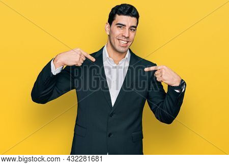 Handsome hispanic man wearing business clothes looking confident with smile on face, pointing oneself with fingers proud and happy.