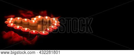 Candles Are Burning In The Dark. Red Candles Are Arranged In The Shape Of A Heart On A Black Backgro