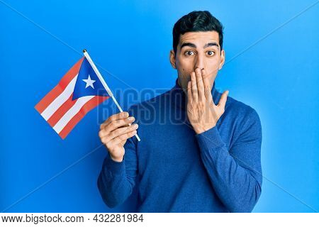 Handsome hispanic man holding puerto rico flag covering mouth with hand, shocked and afraid for mistake. surprised expression