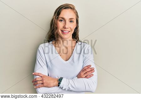 Young blonde woman wearing casual clothes happy face smiling with crossed arms looking at the camera. positive person.