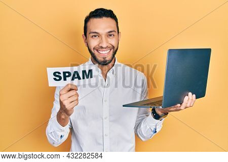Hispanic man with beard working using computer laptop holding spam banner smiling with a happy and cool smile on face. showing teeth.