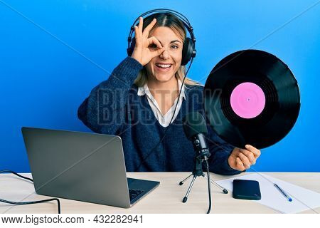 Young caucasian woman working at radio studio holding vinyl disc smiling happy doing ok sign with hand on eye looking through fingers