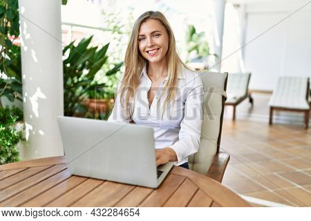 Young blonde woman smiling happy using laptop working at the terrace.