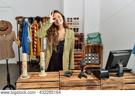 Beautiful hispanic woman working at fashion shop doing ok gesture with hand smiling, eye looking through fingers with happy face.