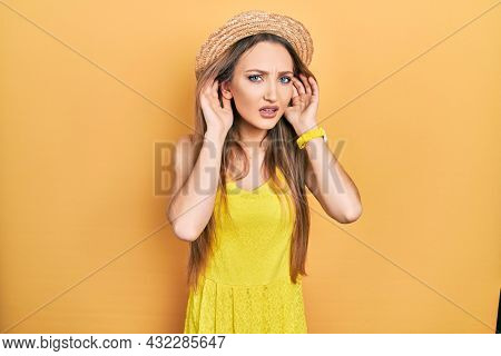 Young blonde girl wearing summer hat trying to hear both hands on ear gesture, curious for gossip. hearing problem, deaf