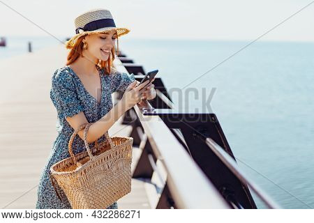 Smiling Beautiful Female Staying On The Pier And Surfing Smartphone On Sunny Day. Wearing Fashionabl