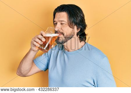 Middle age caucasian man with beard drinking a pint glass of fresh beer
