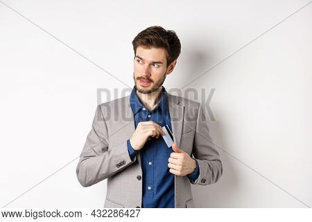 Confident And Successful Businessman Looking Self-assured While Put Plastic Credit Card In Suit Pock
