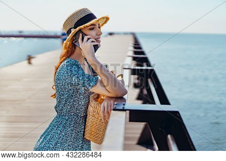 Young Beautiful Redhead Girl Talking On The Smartphone While Standing On The Pier. Wearing In Fashio