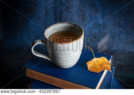 Autumn Reading. A Cup Of Tea And An Autumn Leaf On A Stack Of Books In Front Of A Window With Rain B