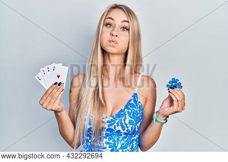 Young beautiful caucasian woman holding poker cards and chips puffing cheeks with funny face. mouth inflated with air, catching air.