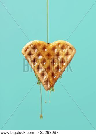 Pouring Maple Syrup Over One Heart-shaped Waffle Against A Green-colored Background. Close-up Of Map