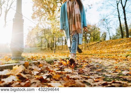 Legs Of Unrecognosable Woman Wearing Brown Boots And Jeans In Autumn Yellow Foliage Walking In Park